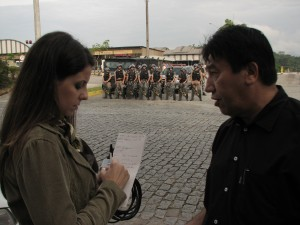 Presidente João Bruggmann sendo entrevistado com a polícia de olho ao fundo
